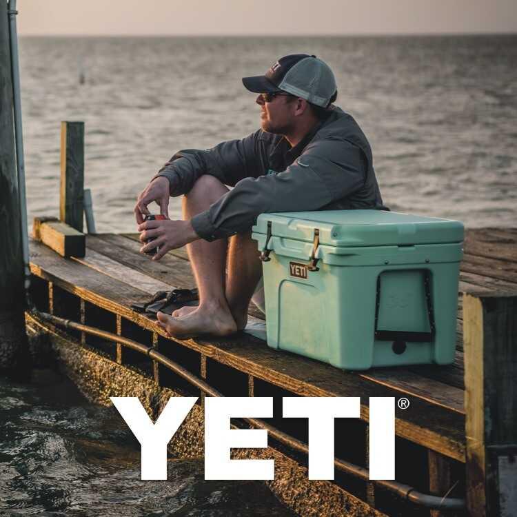 YETI logo with man sitting on dock next to YETI cooler